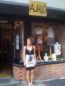Kate in front of her store, with mannequins and clothes in the window