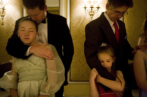 Fathers hug their daughters from behind at a Purity Ball