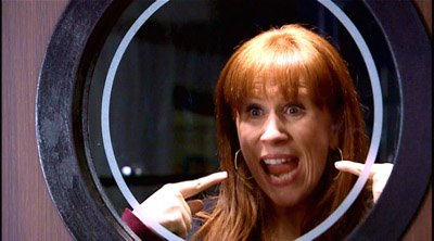 Donna Noble through a window, pointing to herself and grinning, from the series 4 opener