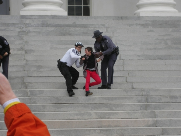Police drag a protester down the steps of the capitol.