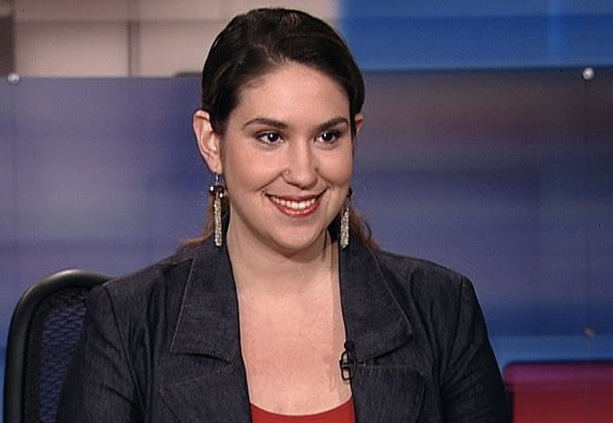 Katie Halper in jacket and red top, wearing earrings and hair in a ponytail