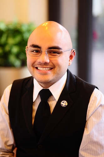 Greg smiling, wearing glasses, black vest and black tie