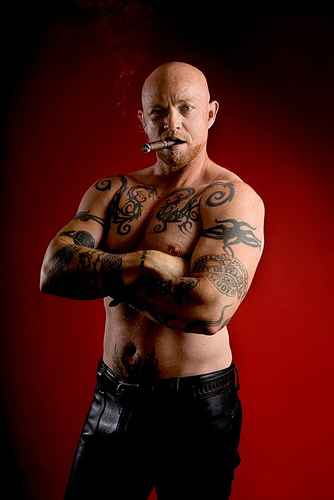 Buck Angel topless, arms crossed, chomping a cigar