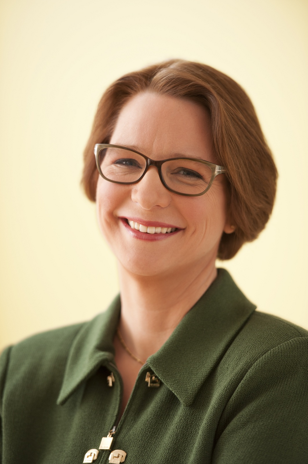 Darcy Burner in green collared shirt, wearing glasses, smiling