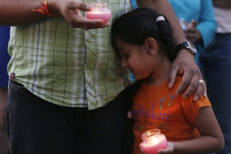 A young girl leans on a man, both holding candles during a vigil