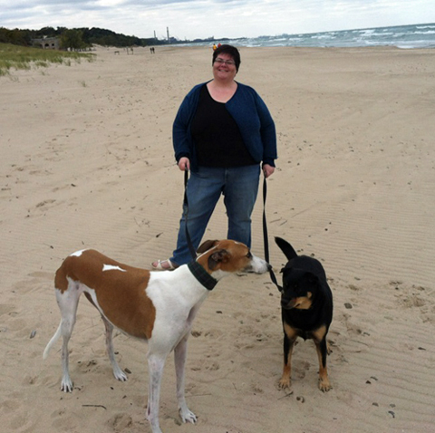 Melissa on the beach with her two dogs