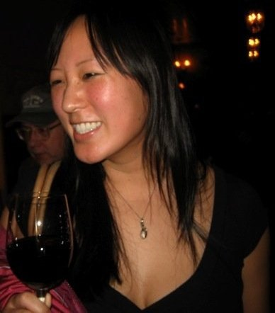 Amy Choi smiling, wearing black shirt and holding red wine glass