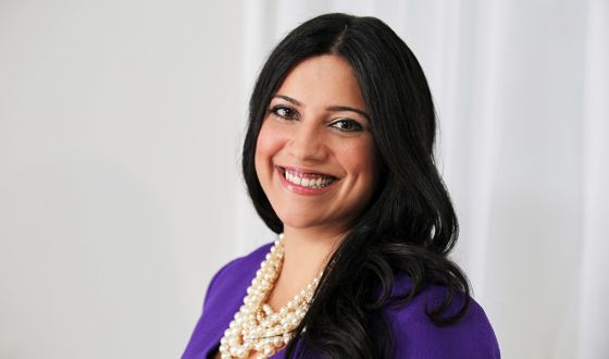 Reshma smiling, long black hair with purple jacket and pearls