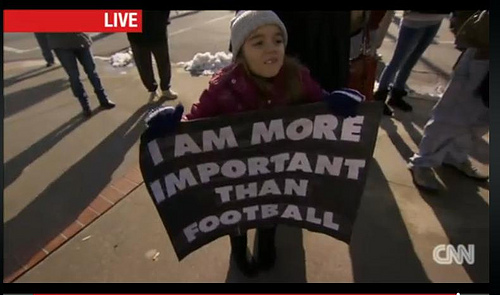 Young girl holding a sign that says I am more important than football