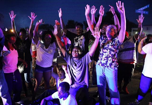 People of ferguson with their hands raised, lights on them at night