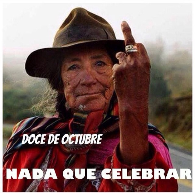 "An indigenous woman wearing red clothing and a felt hat flips off the camera. Image reads: ""The 12th of October is nothing to celebrate!"""