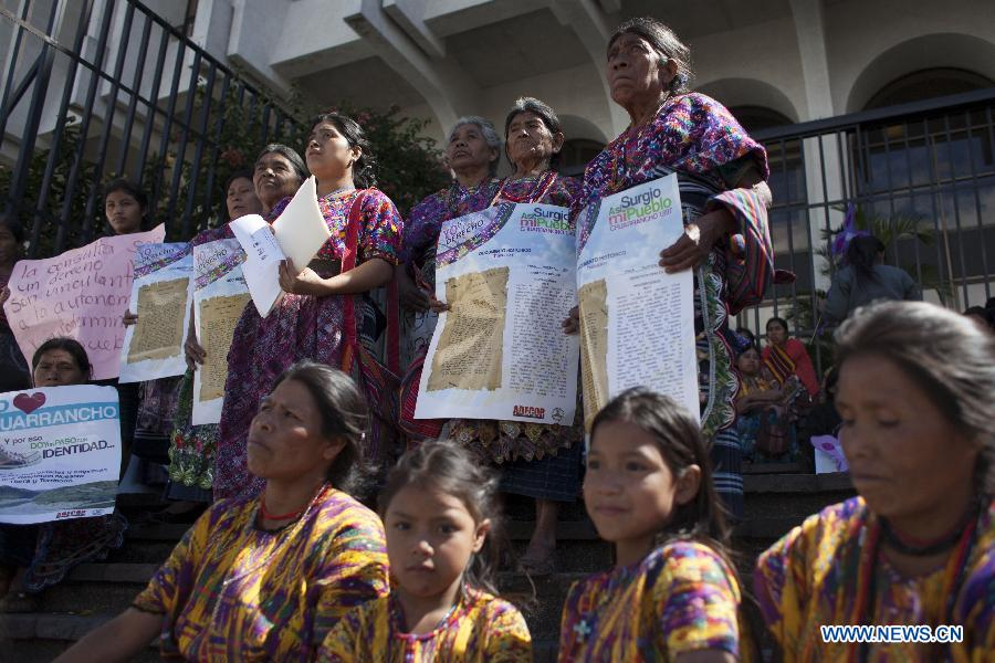 Indigenous Guatemalan women stand holding signs in protest of the cement factory.
