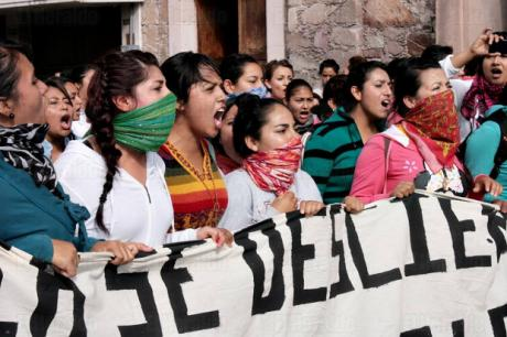 A line of young women holding a banner, their mouths open in protest. They are wearing bandanas on their faces, and many of them have their hair braided.