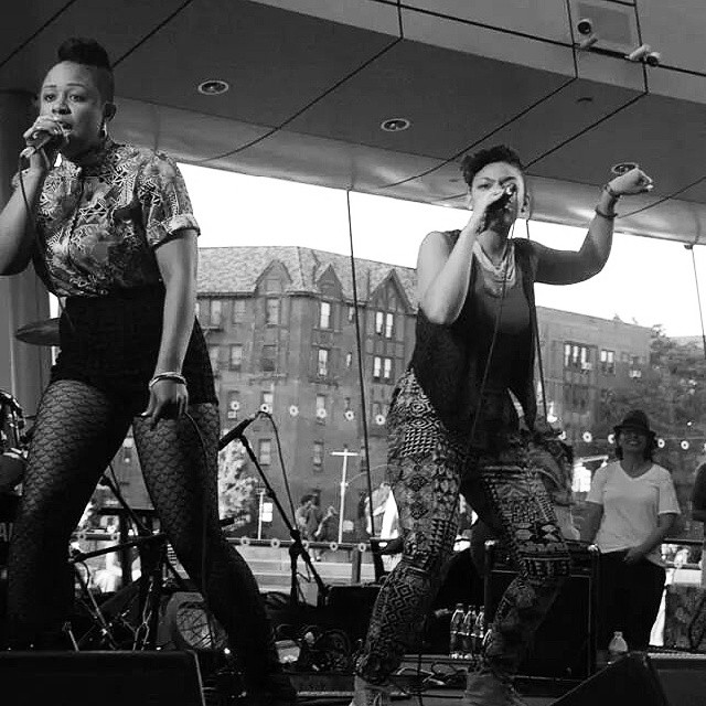 Two fly black women holding mics in the middle of a performance