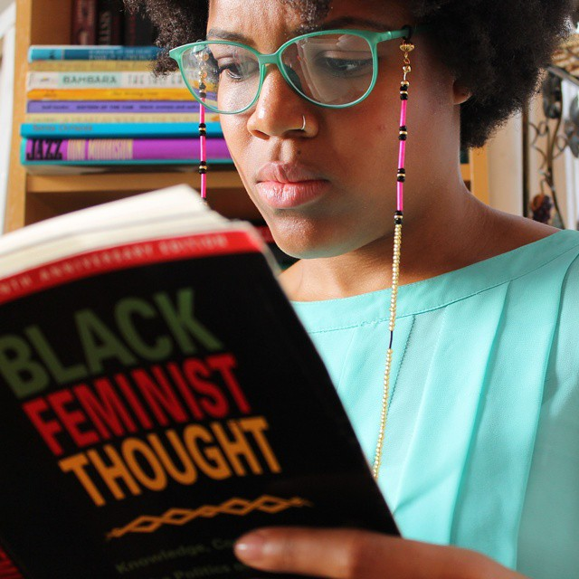 Black woman wearing glasses with a beaded glasses chain reading Black Feminist Thought