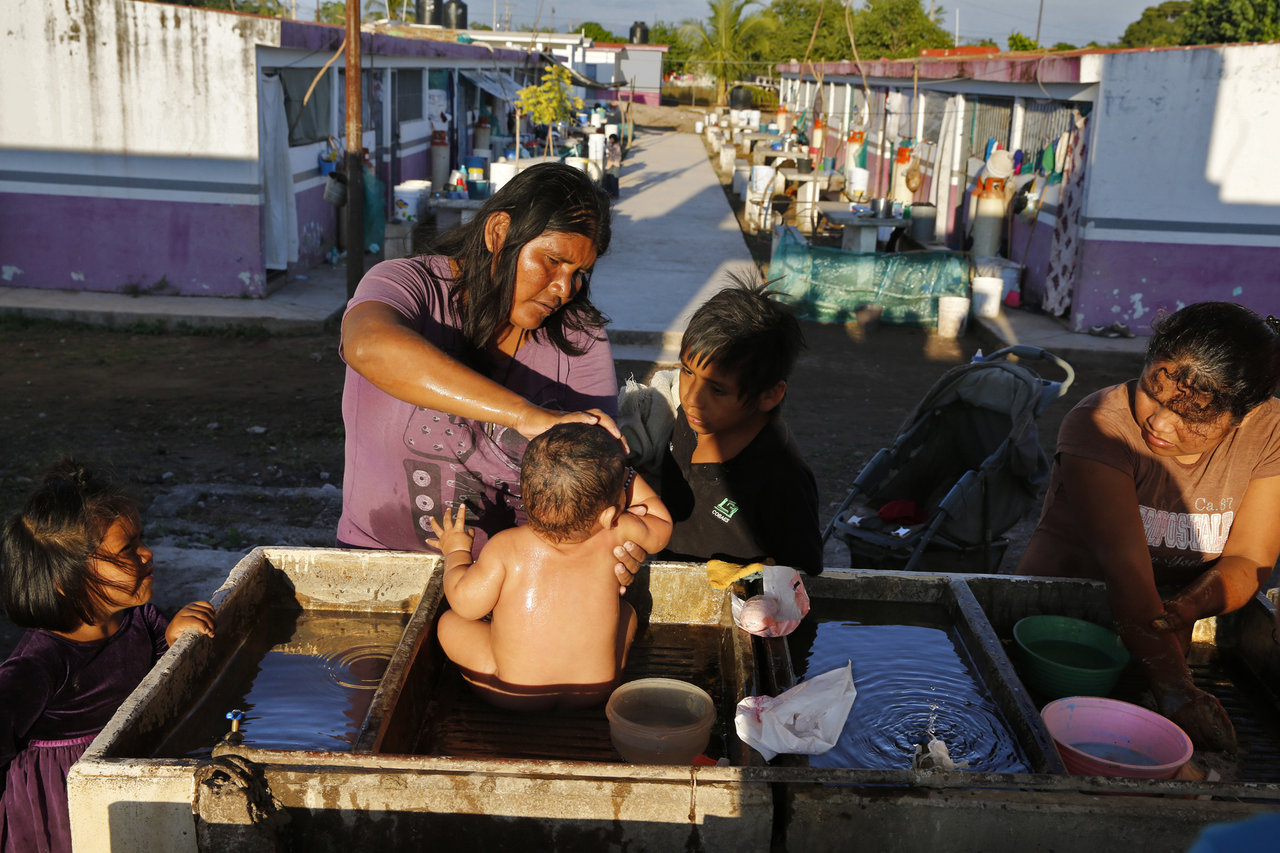 Diaz Matia bathes her 9-mo-old son where people wash dishes and clothes in a government-run farm worker camp in Isla del Bosque, Sinaloa, Mexico.