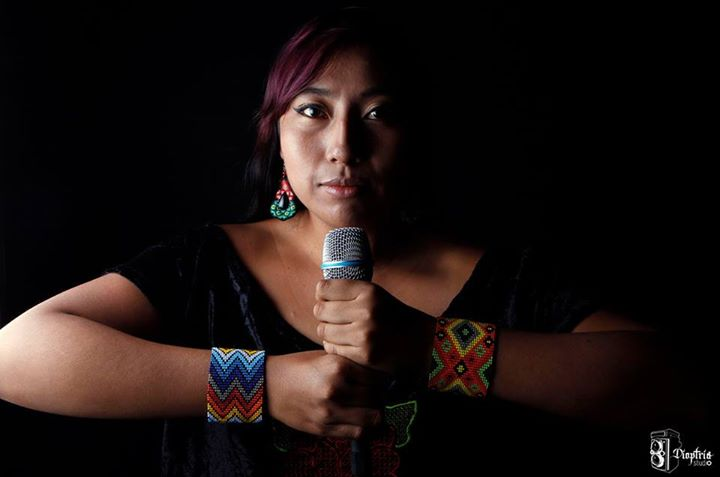 Mare holds a microphone with both hands, her face only half lit. She is wearing colorful bracelets and earrings.