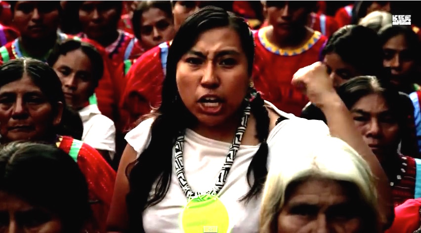 Mare has on a fierce face, rapping while surrounded by older Triqui women.