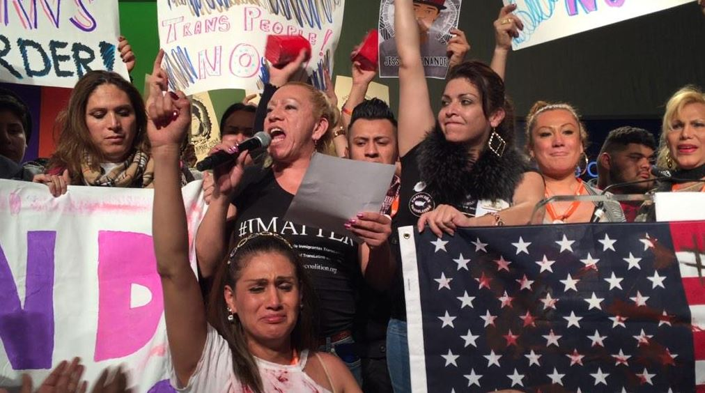 Trans activist Bamby Salcedo on the mic surrounded by Trans WOC with fists up.