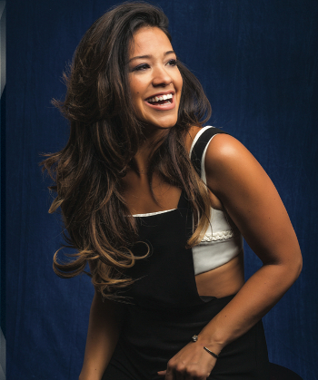 Gina Rodriguez poses for the camera in a pair of overalls.