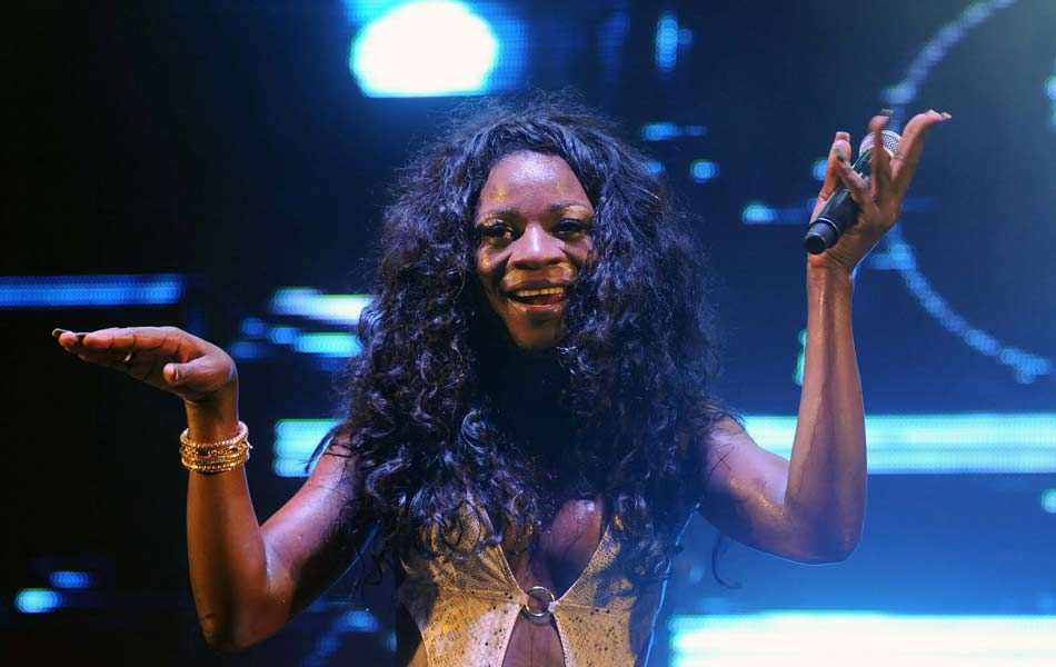 Black trans woman with long black hair raises her hands up on stage
