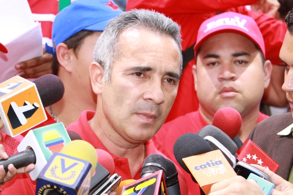 Freddy Bernal, a man with short grey hair, wearing a red polo shirt and in front of press microphones