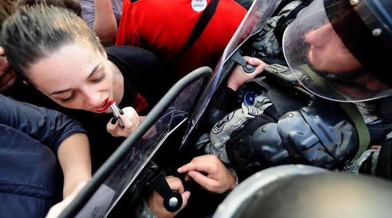 Badass woman protester in Macedonia uses a riot shield as a mirror to reapply her lipstick