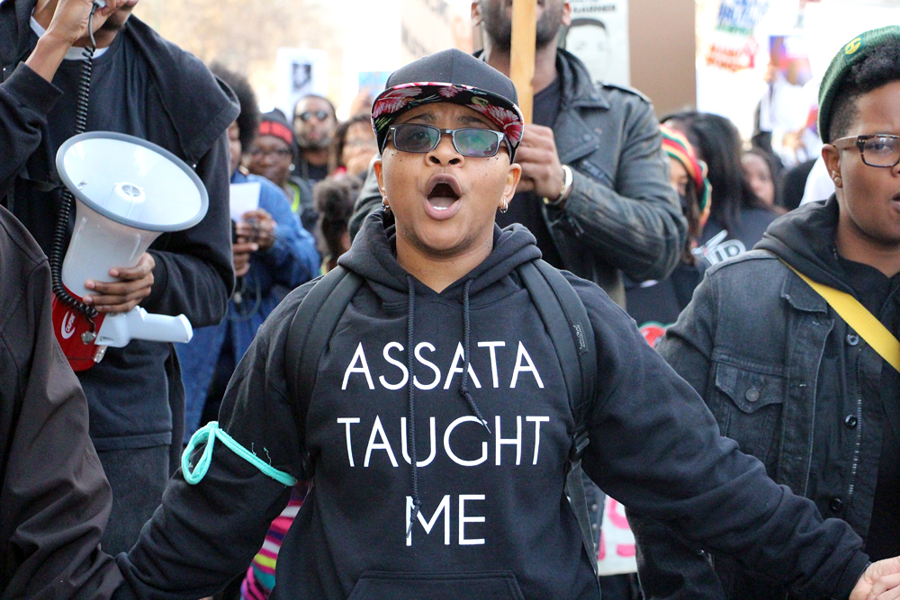 Protester wearing an Assata Taught Me hoodie