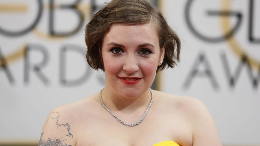 lena dunham (a white lady with chin length brown hair, wearing a strapless yellow thing and pearls)