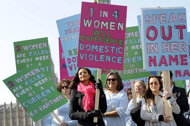 "Image of women carrying signs at a protest that read ""1 in 4 women will experience domestic violence"""