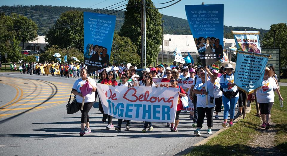 "100 women in matching t-shirts walk along the side of the road, holding signs that say ""We Belong Together."""