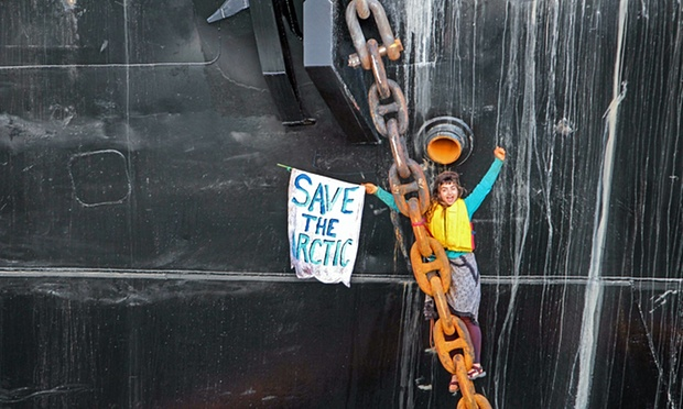 "A young woman hanging off of a thick anchor chain raises her hands in a gesture of triumph. She's holding a sign that says ""Save the Arctic."""