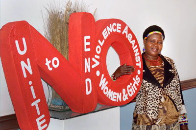 "Senior Chief Inkosi Kachindamoto standing next to a large red cutout that reads ""NO"" with words inside of the letters that read ""Unite to end violence against women and girls"""