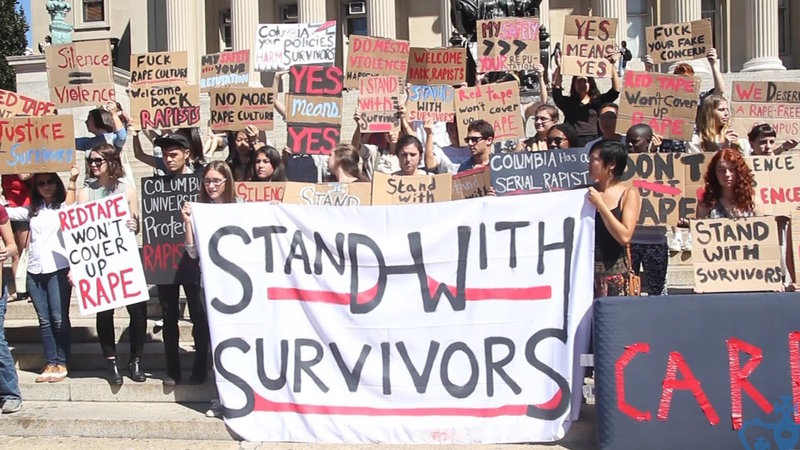 protestors with stand with survivors sign