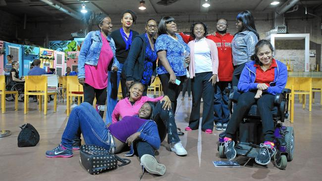 A group of young disabled women of color, some sitting, some standing, one in a powerchair.