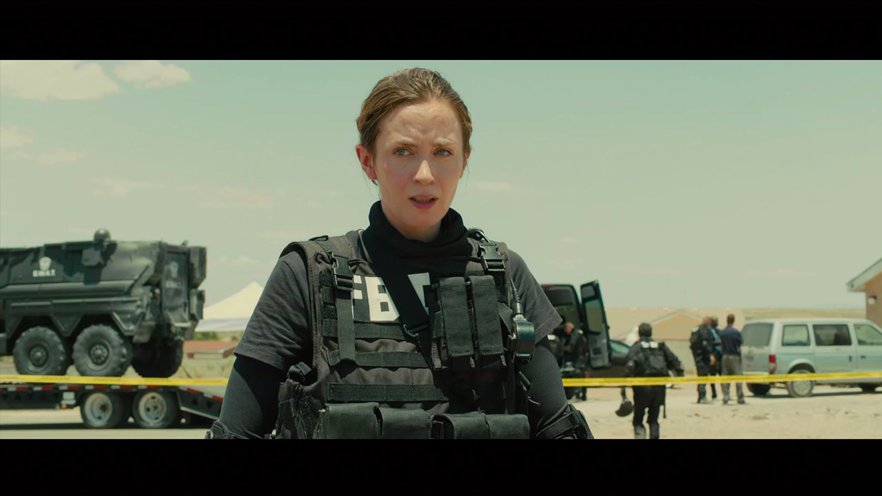 Actress Emily Blunt, woman with dark hair and fair skin standing in the open air of a crime scene in the desert, and wearing FBI gear