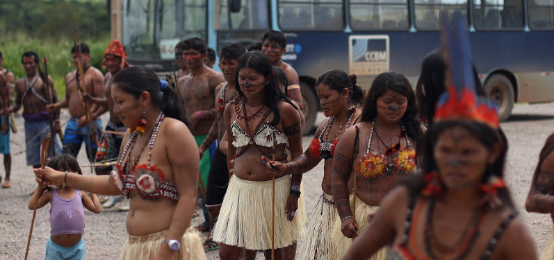 Indigenous women from the Xingu River walk wearing traditional grass skirts.