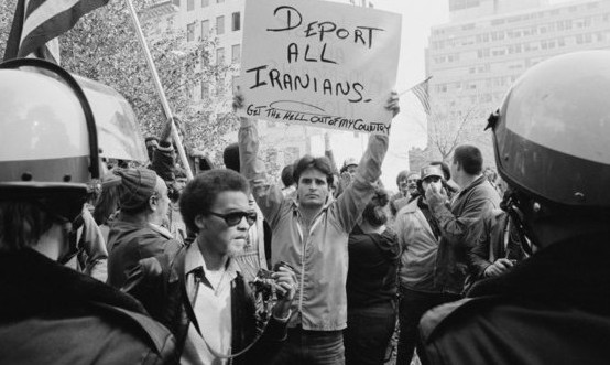 "Man holds sign saying ""Deport Iranians"""