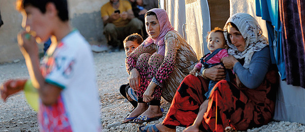 Two refugee women and children sit on a stoop, looking tired and hungry.