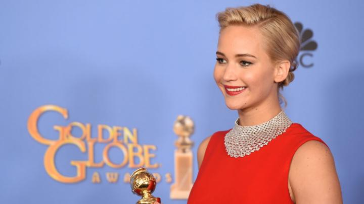 Jennifer Lawrence poses with a Golden Globe. She's wearing a floor length red dress and has her blonde hair back in a bun.