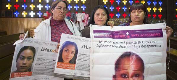 Three women hold photos of their daughters, disappeared in Juarez.