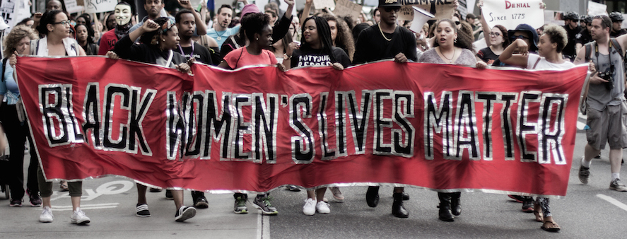 "A line of protestors march holding a sign that says ""Black women's lives matter."""