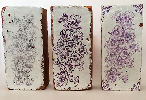 Bricks painted in white and blue with images of pansies