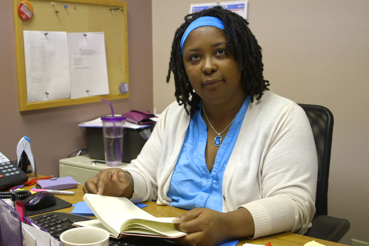 A black woman wearing scrubs, with locs in a headband, looks at the camera while at her desk. She is an abortion provider.