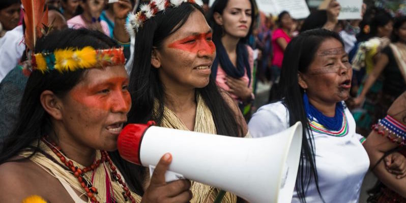 Three indigenous women walk, arms linked, faces painted. One of them is holding a megaphone.
