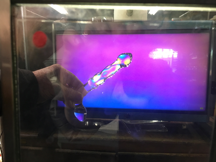A glass dildo under a polariscope showing rainbow colors