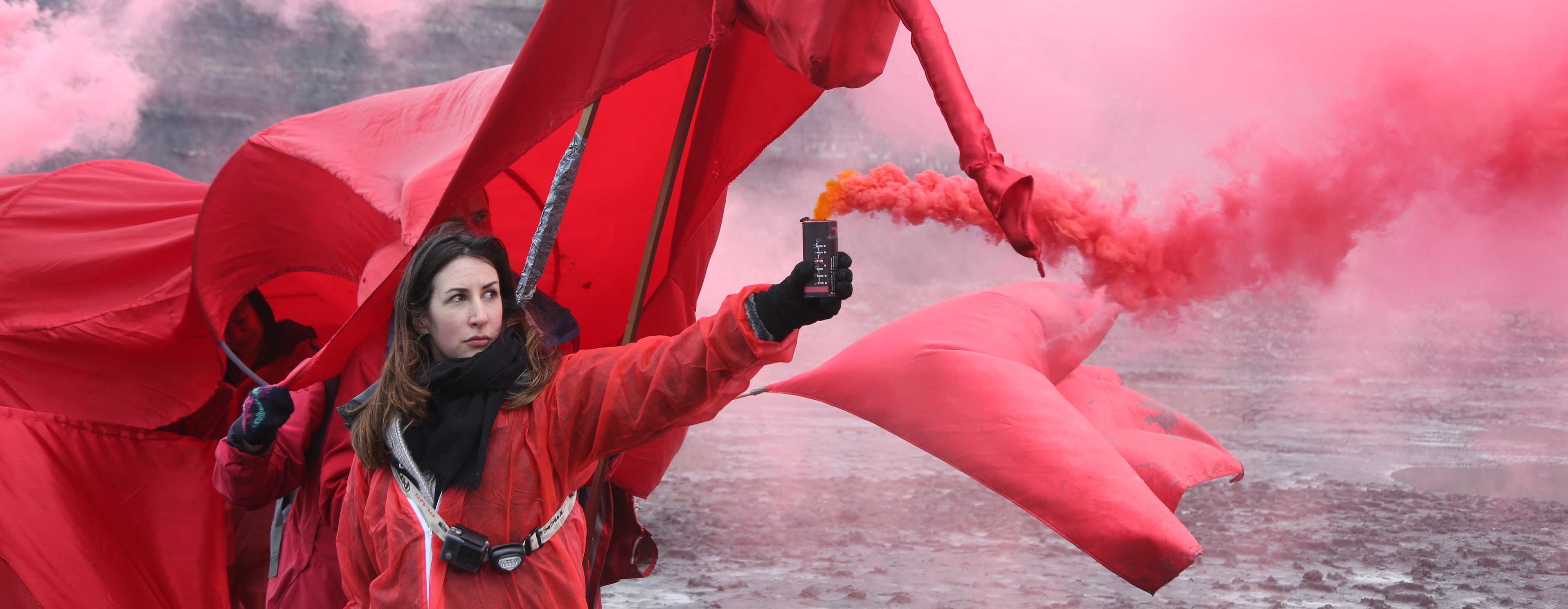 A woman dressed in red looses a canister of red smoke.