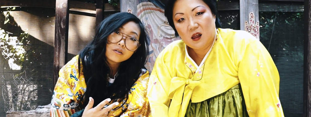A still from the music video, Margaret Cho and Awkwafina pose in yellow kimonos.