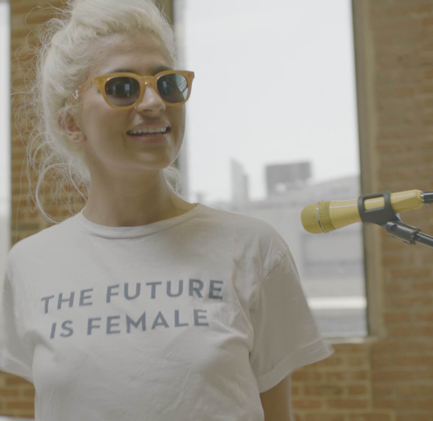 "Kiran wears sunglasses and a ""the future is female"" white t-shirt"