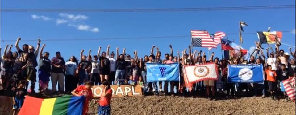 A group of 50+ protestors stand on a mound of dirt holding flags, their fists in the air.